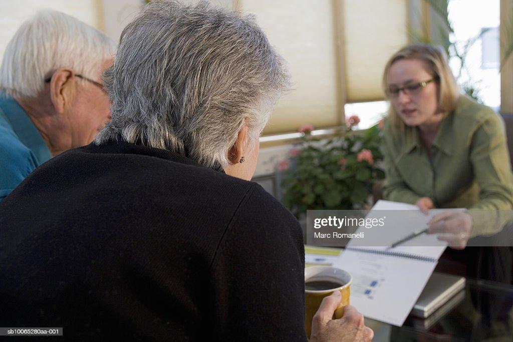 Three people talking around table : Foto stock