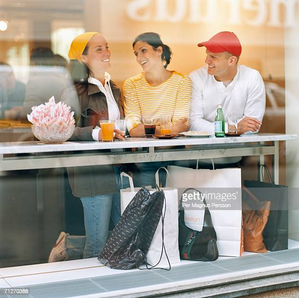 Three people talking in a cafe.