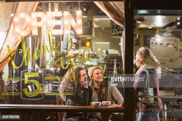 Tres personas hablando en la cafetería