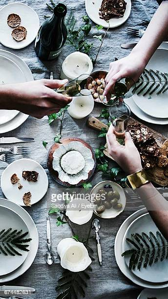 three people toasting above table - dinner party stock pictures, royalty-free photos & images