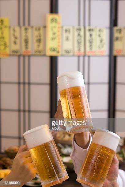 Three People Toasting with Beer at Izakaya