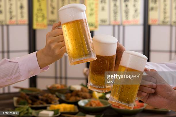Three People Toasting with Beer at Izakaya