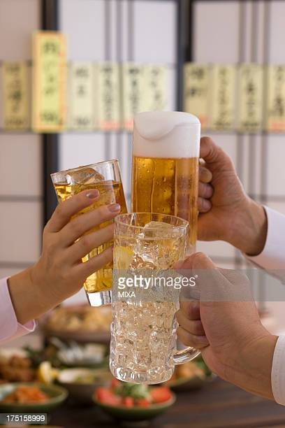 Three People Toasting with Each Other With Various Drinks at Izakaya