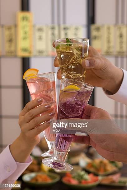 Three People Toasting with Various Cocktails at Izakaya