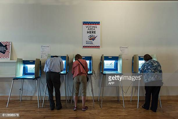Three people vote in booths at the Early Vote Center in northeast Minneapolis Minnesota on October 5 2016 Voters in Minnesota can submit their ballot...