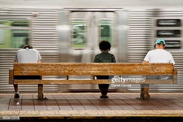 three people waiting for the subway sitting on a bench. 135 st. station, new york, usa - new york city subway stock pictures, royalty-free photos & images