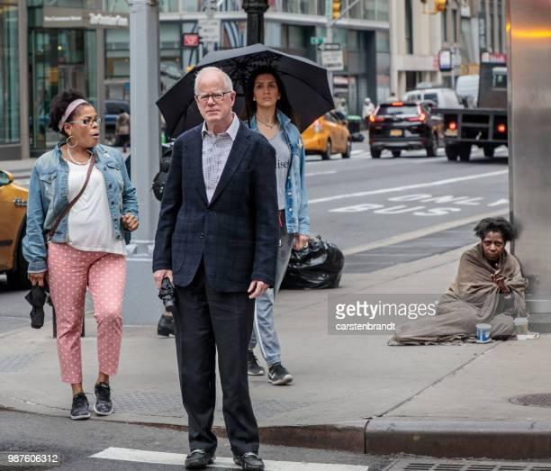 drie mensen te wachten voor het verkeerslicht en een vergadering op de stoep - armoede stockfoto's en -beelden