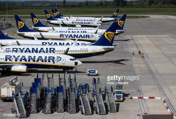 Three people walk on the runway amongst parked and temporarily out of service Ryanair passenger aircraft at Stansted Airport on April 15 2020 in...