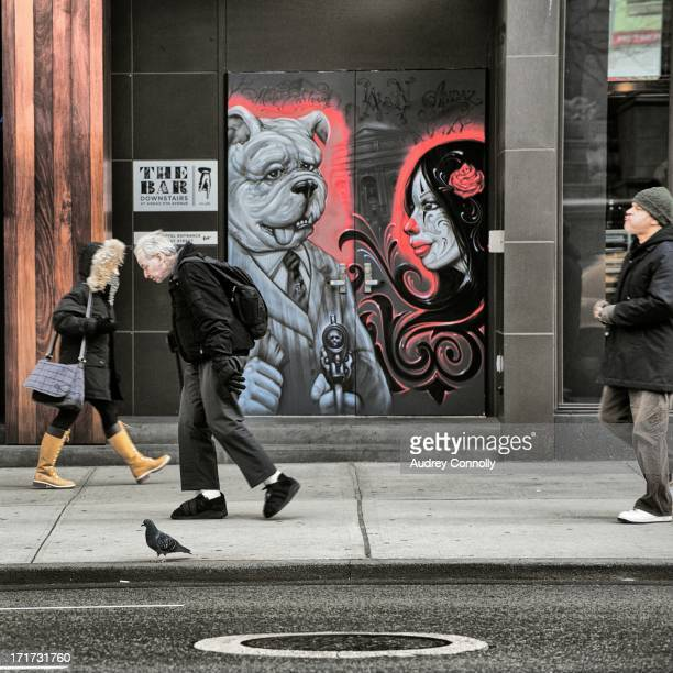 "Three people walk past a mural of a bulldog and dias de los muertos woman at ""the bar"" on 5th Avenue in Midtown, Manhattan, New York City"