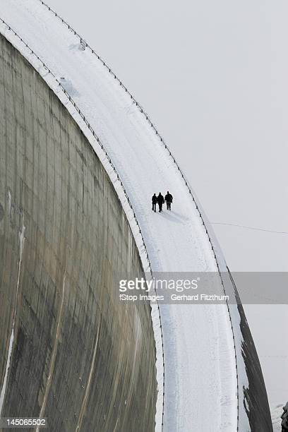 Three people walking above the Zervreila Dam, Switzerland