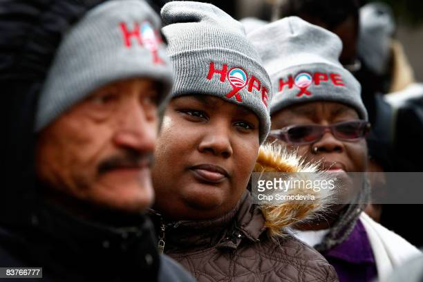 Three people wear hats inscribed with the word hope with the Barack Obama presidential campaign's trademark logo of the rising sun as about 1000...