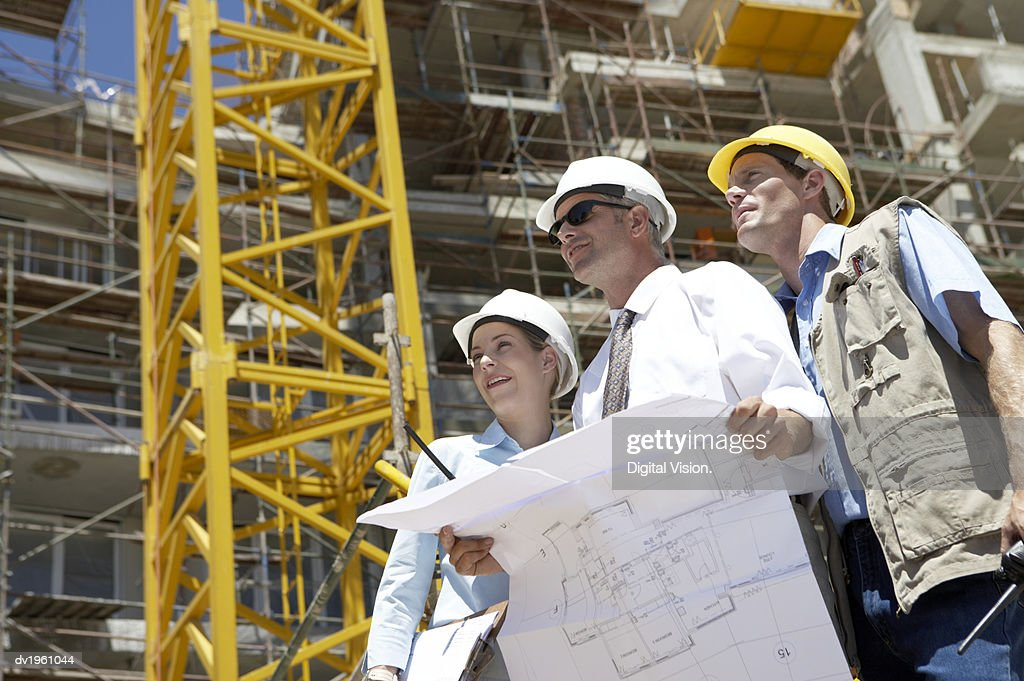Three People Wearing Hard Hats on a Building Site, with One Man Wearing Sunglasses and Holding Blueprints : Stock Photo