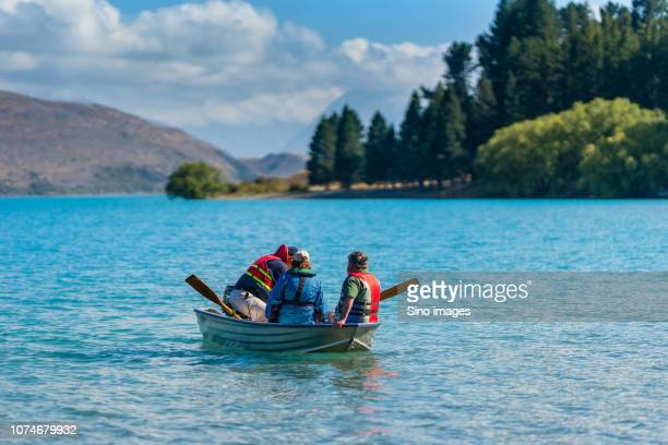 three people wearing life jackets sitting in rowboat on scenic river, new zealand - image stock pictures, royalty-free photos & images