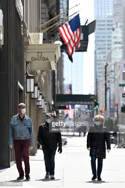 Three people wearing protective masks and gloves walk past closed retail stores on fifth Avenue amid the coronavirus pandemic on April 12 2020 in New...
