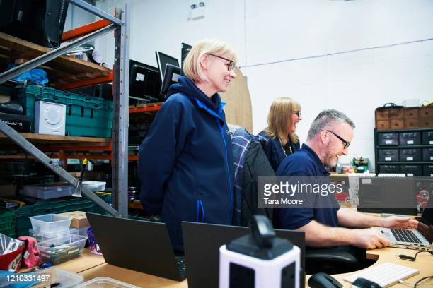three people working in computer recycling centre - femalefocuscollection stock pictures, royalty-free photos & images