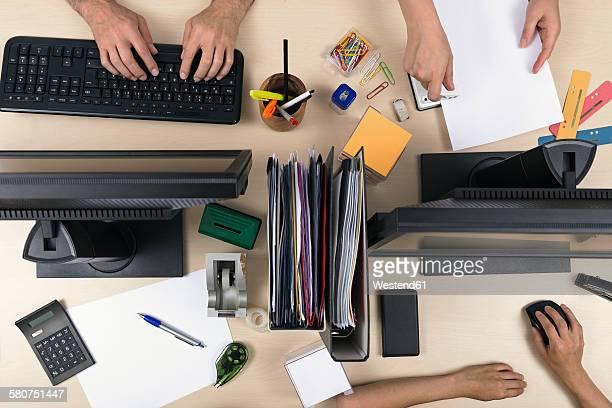 Three people working on desk