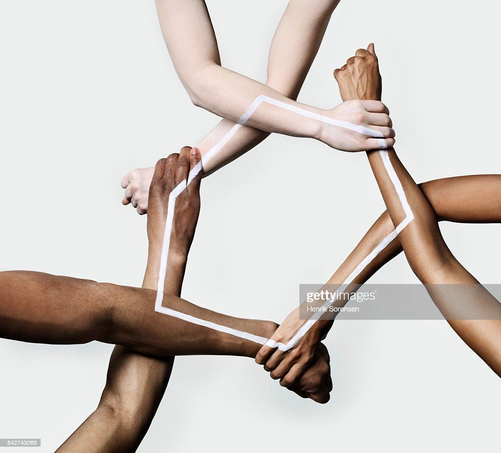 Three peoples hands and arms forming a triangle : Stock-Foto