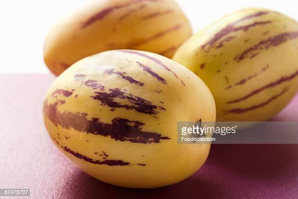 three pepino melons on purple background - pepino stock pictures, royalty-free photos & images
