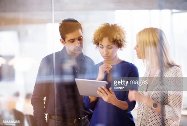 Three persons, looking at tablet computer
