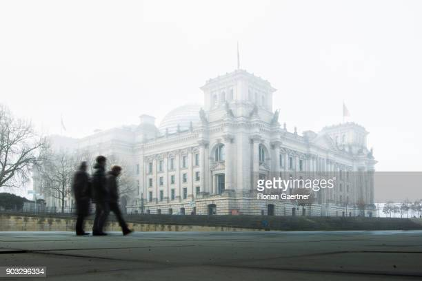Three persons walk along the river Spree in front of the Reichstag building on January 10 2018 in Berlin Germany