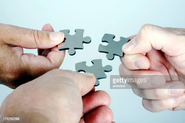 Three Persons with Puzzle in Hand Coming Together