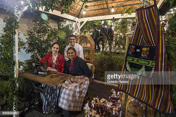 Three persons with the Madeira Island traditional costume poses for the picture in the city during Christmas celebrations on December 29, 2016 in...