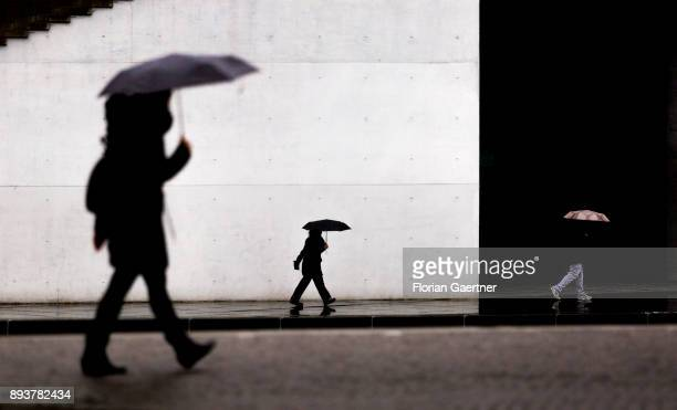 Three persons with umbrella walk along the river Spree on December 15 2017 in Berlin Germany