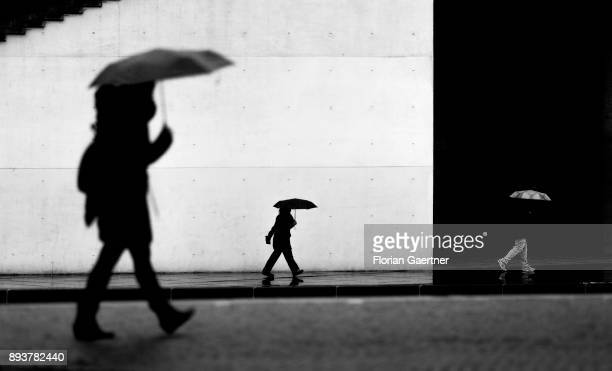 Image has been converted to black and white BERLIN GERMANY DECEMBER 15 Three persons with umbrella walk along the river Spree on December 15 2017 in...