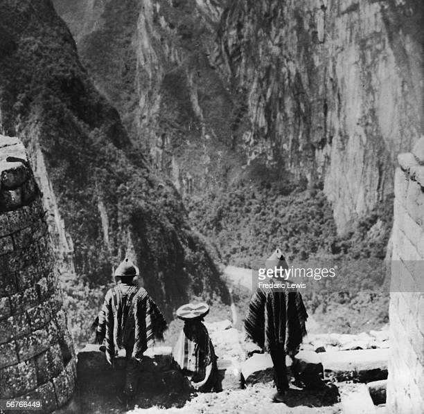 Three Peruvian Indians stand in traditional dress on a masonry ledge of the ancient Incan city of Machu Picchu and look out over a deep valley at one...