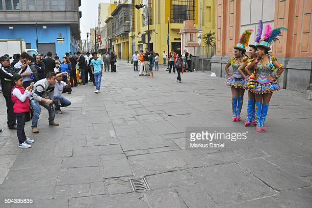 CONTENT] Three peruvian women in front of tourists locals and photographers are showing their typical colorful costumes in front of the basilica...