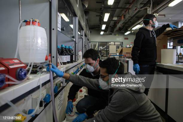 Three PhD students wearing gloves and protective face masks are pictured at work inside the laboratory of Chemistry Materials and Chemical...