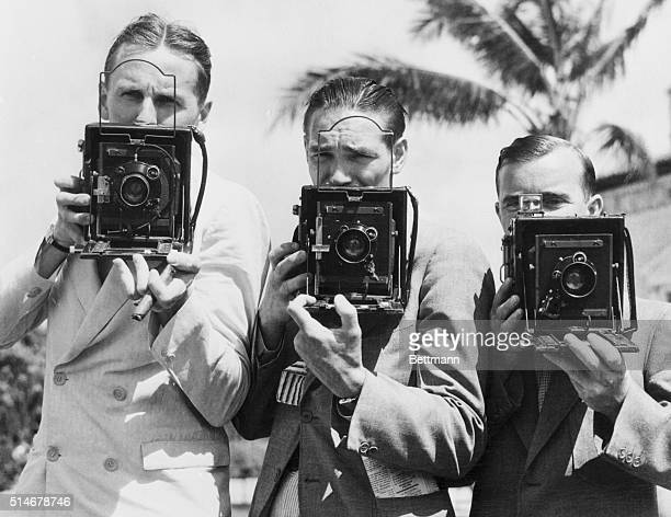 Three photographers in the Roosevelt press corps aim their cameras in Coral Gables, FL., while awaiting FDR's return from a fishing holiday. From...