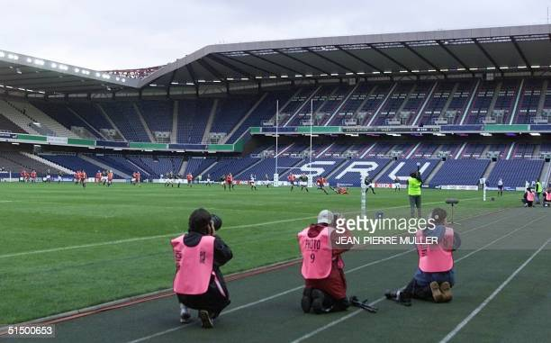 Three photographers take pictures of the Rugby World Cup firstround match between South Africa and Spain 10 October 1999 at the almost empty...