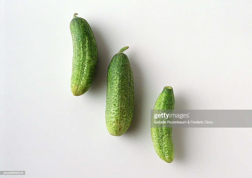 Three pickle cucumbers in diagonal line, white background : Stock Photo