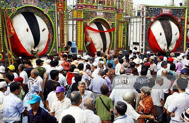 Three pig gods are displayed in front of the Yimin Temple in Hsinchu northern Taiwan 17 August 2003 while the Haka people celebrate the Ghost...