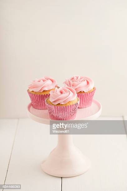 Three pink cup cakes on a cakestand
