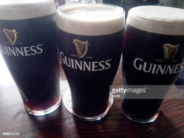 three pints of british stout - guinness stock photos and pictures