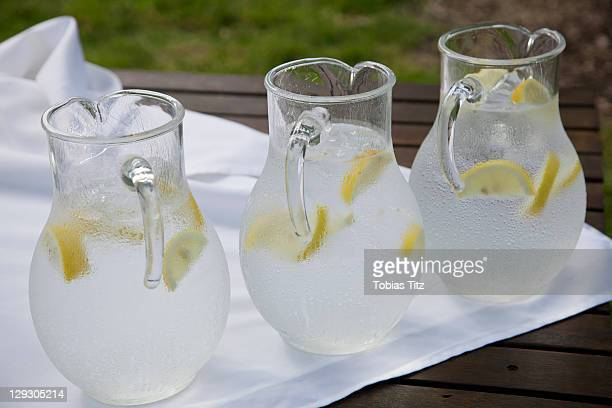 Three pitchers of ice water with lemon slices