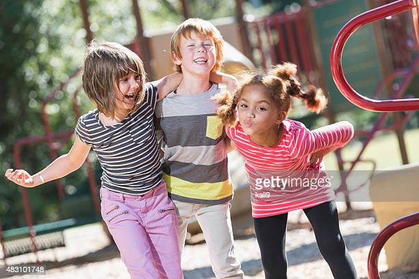 Three playful multiracial children on playground