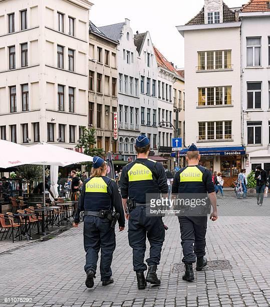 three police are walking in the streets of antwerp,belgium - antwerpen stad stockfoto's en -beelden