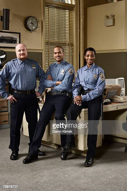 Three police officers in police station, smiling, portrait