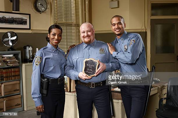 Three police officers, one holding award, portrait