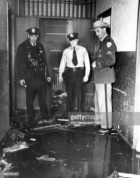Three policemen looking at the damage caused during the riot at the Crownsville State Hospital at the time known as the 'Hospital for the Negro...
