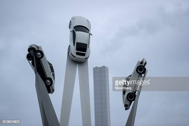Three Porsche 911 automobiles stand elevated on a sculpture outside the Porsche AG factory in Stuttgart Germany on Friday Jan 26 2018 Porsche AG will...