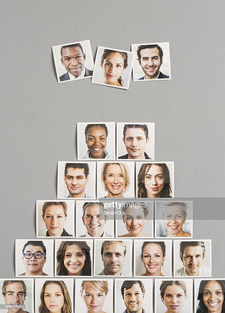 Three portrait prints above pyramid of others : Stock Photo