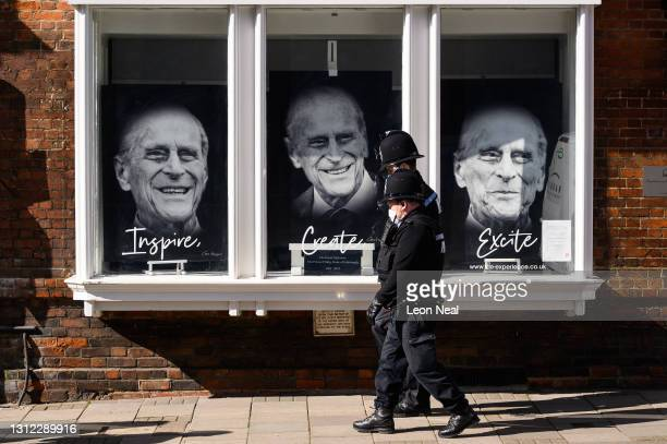 Three portraits are seen in a gallery window as tributes continue to be made to Prince Philip, Duke Of Edinburgh who died at age 99 on April 13, 2021...