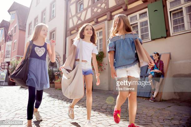 three pre-adolescent girls walking through a shopping town in germany - ハーフティンバー様式 ストックフォトと画像