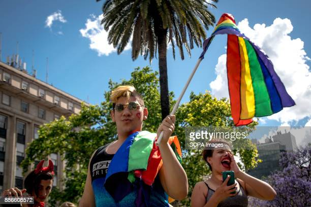 Three pride supporters wave rainbow flags and chant slogans in front of iconic Plaza de Mayo buildings Thousands of pride supporters marched from...