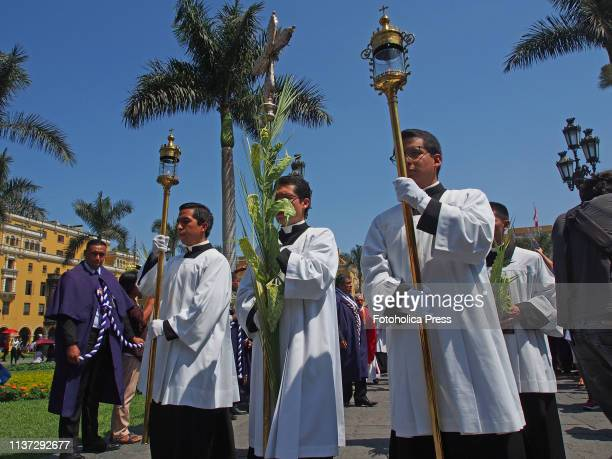 Three priests carry on a religious procession at Lima downtown on Palm Sunday of the 2019 Holy Week
