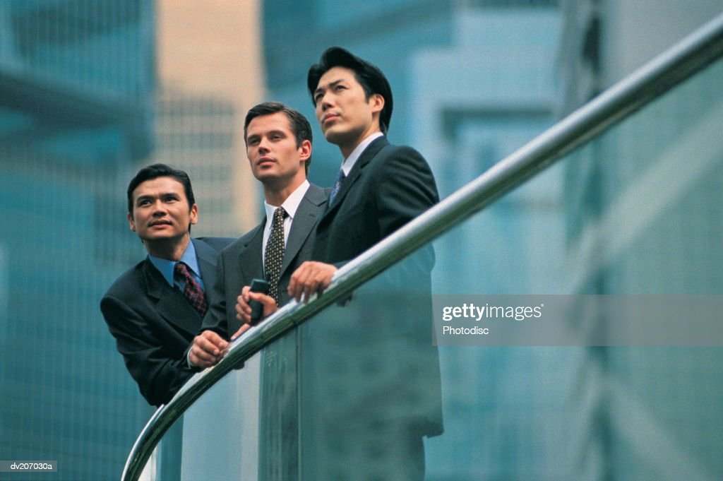 Three professionals leaning on banister : Stock Photo
